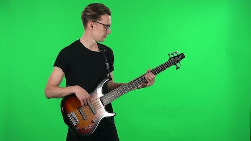 Portrait Professional Musician Playing the Electric Bass. Young Guy with Glasses and a Black T
