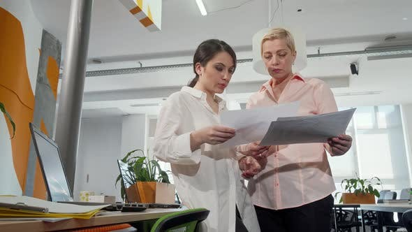 Thumbnail for Low Angle Shot of Two Businesswomen Examining Documents at the Office