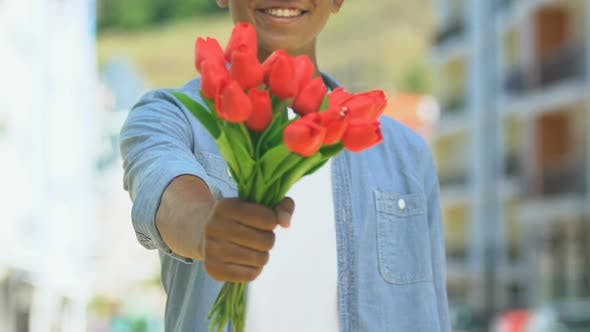 Positive Man Giving Flowers Into Camera