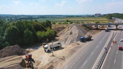 Heavy machinery with stones. New road with moving transport near the piles with stones.