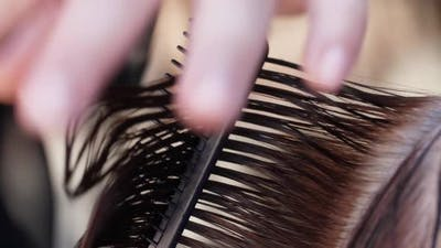 Hairdresser Cuts the Hair of a Woman