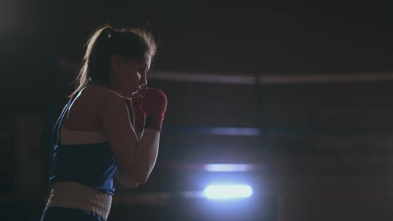 Cover Image for A Beautiful Woman Conducts a Shadow Fight Practicing Technique and Speed of Strikes While Training