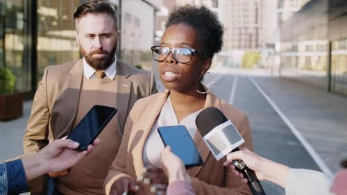 Black Woman Giving Interview to Journalists Outdoors on Street