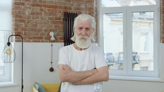 Thumbnail for Senior Bearded Man with Wrinkled Face in Home Clothes Poses on Camera
