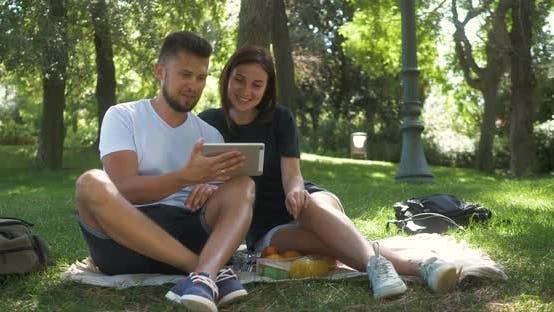 Thumbnail for Ernstes junges Paar oder Freunde mit digitalem Tablet in Park. Mann Frau liegend auf Gras und