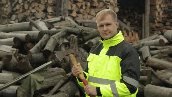 Thumbnail for Lumberjack in Reflective Jacket. Man Woodcutter with Small Axe. Sawn Logs, Firewood Background