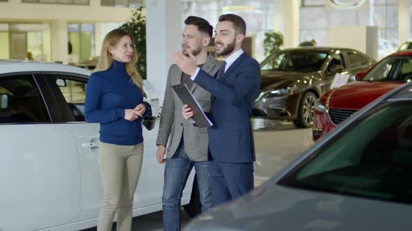 Thumbnail for Cheerful Salesman Showcasing Cars to Couple