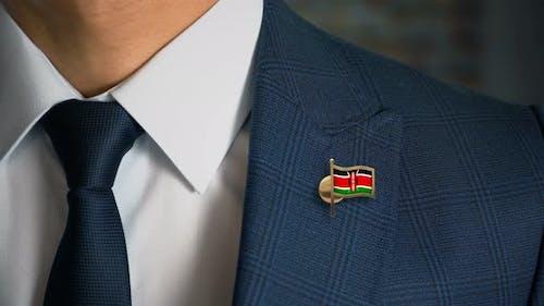Homme d'affaires marchant vers la caméra avec drapeau du pays épingle Kenya