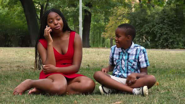 Thumbnail for A Young Black Mother and Her Son Sit on Grass in a Park, the Son Tries To Attract the Attention