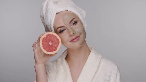 Thumbnail for Happy Girl After Spa with Facial Mask Playing with Fresh Pomelo