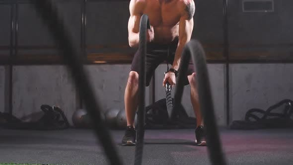Thumbnail for Handsome Muscular Bare-chested Gym Man with Battle Ropes Exercise in the Fitness Gym. Slow Motion