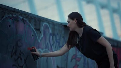 Girl Painting Graffiti on Urban Street. Woman Using Spray Bottle for Graffiti