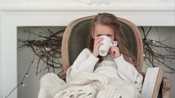 Thumbnail for Little Girl Sitting in a Cozy Chair Wrapped in a Blanket Drinking Tea Near Christmas Fireplace