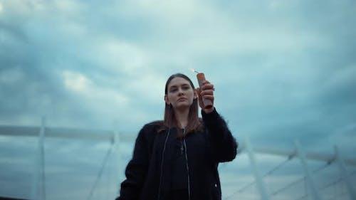 Girl Lighting Smoke Bomb with Lighter on Street, Woman Looking at Smoke Grenade