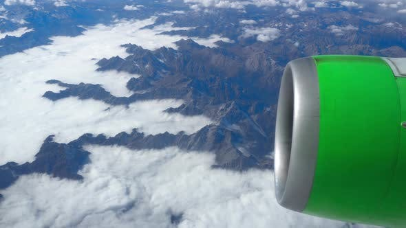 Cover Image for Beautiful view through airplane window, airplane flying above the clouds and mountains