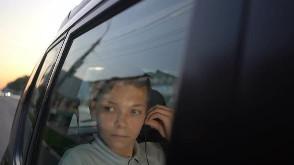 Thumbnail for Teenager Boy with Headphones Listening To the Music in Backseat of Car and Looking Away