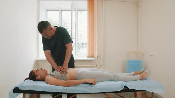 Osteopath Treatment - the Doctor Pushing on the Chest of Young Woman
