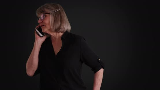 Thumbnail for Mature Caucasian woman communicating on smartphone on grey background