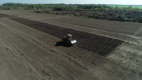 Heavy Roller Compactor is Driving Across the Field Leveling the Soil