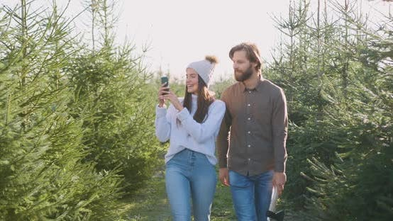 Thumbnail for Couple Walking Together Near Beautiful fir Trees, Woman Making Photos