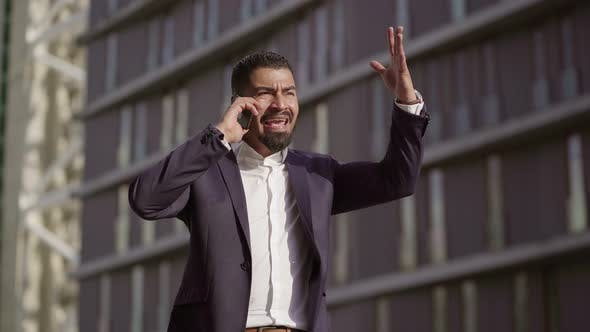 Thumbnail for Emotional Businessman Talking By Smartphone and Gesturing