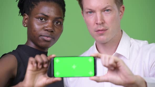 Thumbnail for Two Young Multi-ethnic Business Couple Showing Phone Together