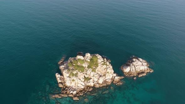 Kleines Boot und kleine Insel im Meer