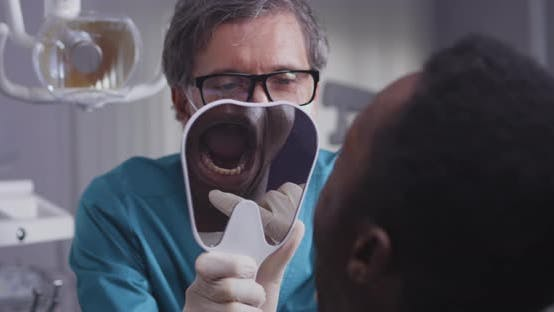 Thumbnail for Dentist Consulting Black Man in Clinic