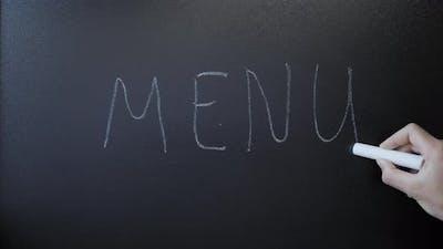 Hand writes word Menu on chalkboard. Menu written on black sign board