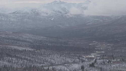 Aerial helicopter flyover above Alaskan bay, past forests and inlets, beaches, drone footage