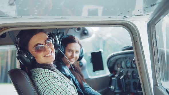 Thumbnail for Young Attractive Girls in an Airplane at the Helm.