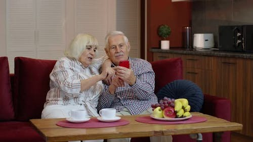 Senior Old Couple Grandparents Talking and Using Digital Mobile Phone at Home. Online Shopping