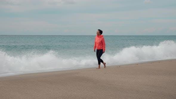 Woman walking on sady stormy beach