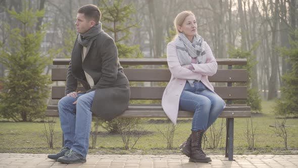 Thumbnail for Angry Caucasian Man and Woman Sitting Back To Back on Opposite Sides of Bench Outdoors. Unhappy