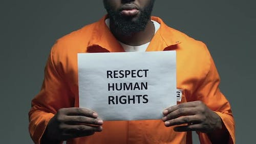 Respect Human Rights Phrase on Cardboard in Hands of Afro-American Prisoner