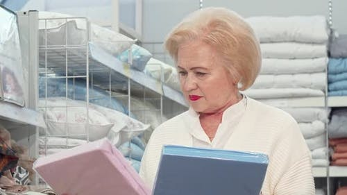 Charming Senior Lady Shopping for Bedding at Furniture Store