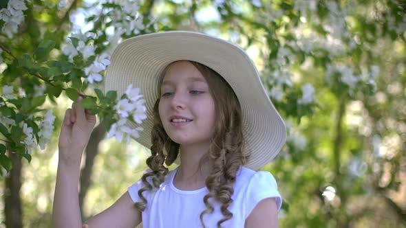 Thumbnail for Romantisches Mädchen schnüffelt blühenden Apfelbaum im Frühlingsgarten am sonnigen Tag. Lächelnd Mädchen Teenager in