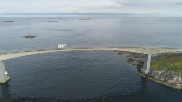 Cover Image for Motorhome Car Travels on Storseisundet Bridge. Atlantic Ocean Road in Norway. Aerial View