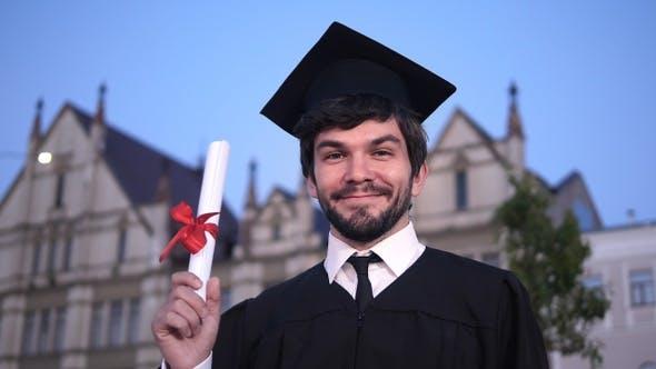 Thumbnail for Caucasian glücklich junge graduierte Mann posiert an die Kamera