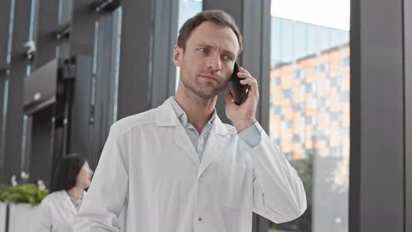 Male Doctor Having Telephone Conversation