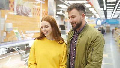 Lovely Married Couple Walk in Grocery Store Choosing Food for Home