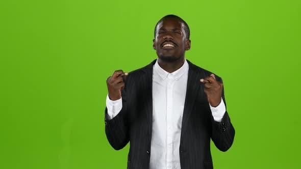 African American Crosses His Fingers, Hopes a Happy Occasion in His Endeavors. Green Screen