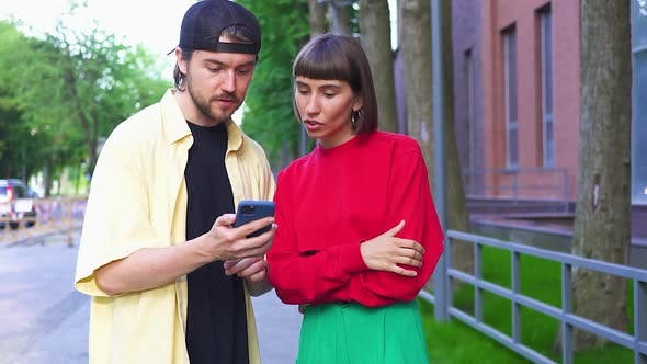 Attractive Couple Using Phone on Street and Getting Wow Gesture Super Happy