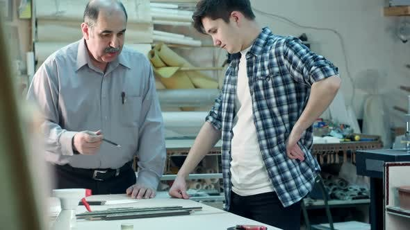 Thumbnail for Senior Male Worker Instructing Young Trainee How To Construct a Frame Behind the Desk