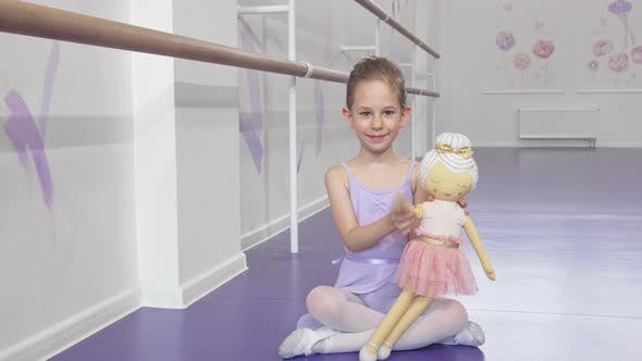 Thumbnail for Full Length Shot of a Lovely Little Ballerina Waving To the Camera Playing with a Doll