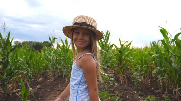 Cover Image for Beautiful Little Girl in Straw Hat Running Through Corn Field, Turning To Camera and Smiling. Happy