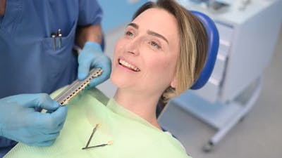 Dentist Checks the Level of Patient's Teeth Whitening with a Dentist's Color. Dental Equipment in