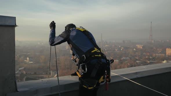 Thumbnail for Heckschuss von Sport-Industriekletterer, Mann in Spezialuniform stehend auf dem Dach, langsam senkt die