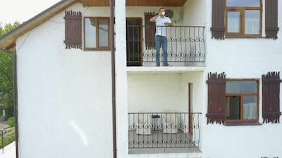 Man Relaxing On Balcony. Handsome man standing out of home on balcony