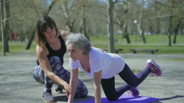 Thumbnail for Smiling Senior Woman with Young Trainer During Workout in Park.